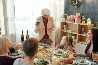 Senior woman with glass of red wine pronouncing festive toast by family dinner