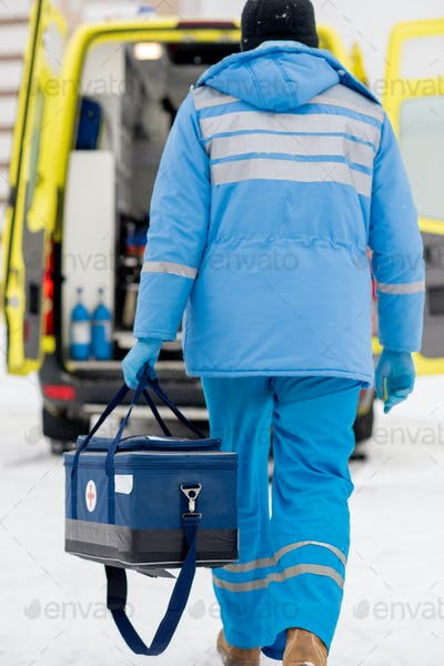 Rear view of paramedic in blue workwear and gloves carrying first aid kit