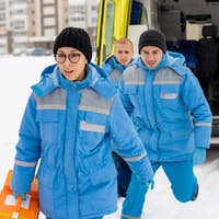 Group of young paramedics in blue uniform hurrying to sick person outdoors