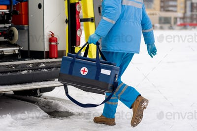 Male paramedic in blue workwear and gloves carrying first aid kit with red cross