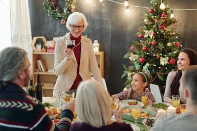 Happy senior woman with glass of wine making Christmas toast by family dinner