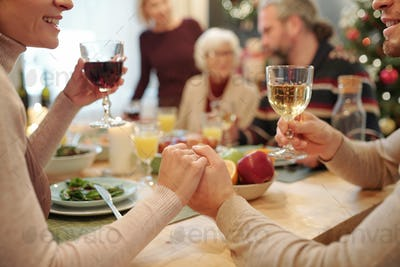 Hands of young affectionate couple with glasses of wine making festive toast
