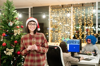 Cheerful female office manager with flute of champagne standing by xmas tree