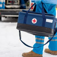 Young paramedic in blue workwear and medical gloves carrying first aid kit