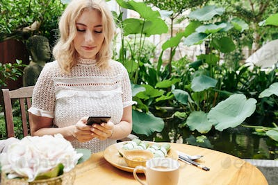 Woman texting and eating lunch