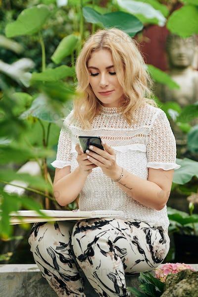 Creative woman checking phone