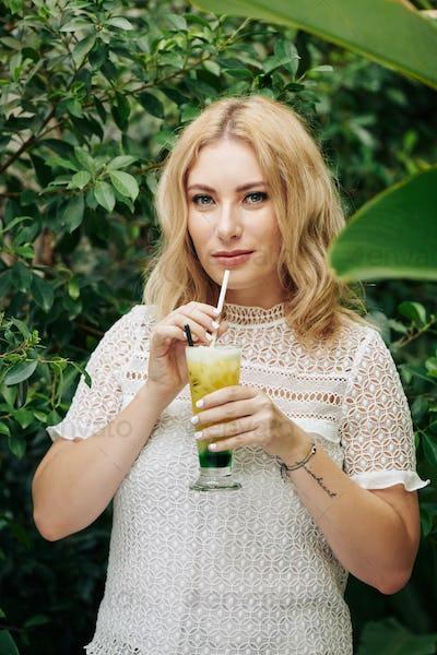 Woman drinking refreshing fruit cocktail