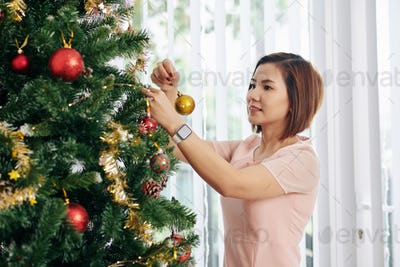 Woman decorating Chirstmas tree