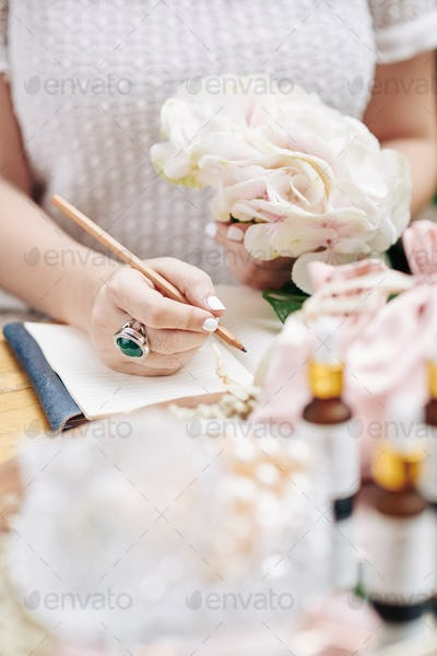 Woman writing ideas for new cosmetics