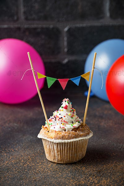 Birthday cupcake with cream and colorful garland