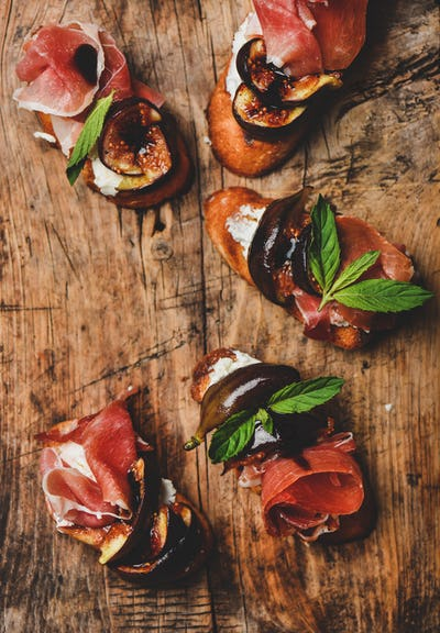 Crostini with prosciutto, cheese and figs on rustic wooden board