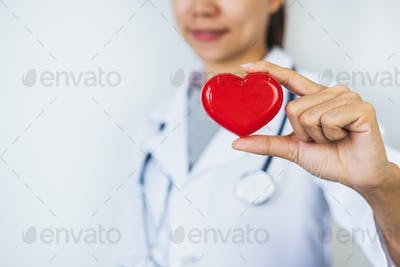Young female doctor with the stethoscope holding red heart, cardiolog healthy care concept