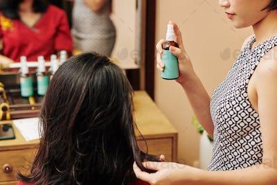 Hairdresser applying moisturizing serum