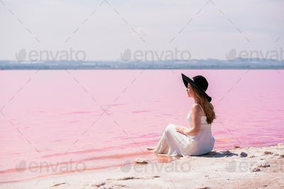cute teenager woman wearing white dress sitting on an amazing pink lake