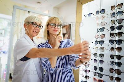 Beautiful woman choosing a glasses in optician store