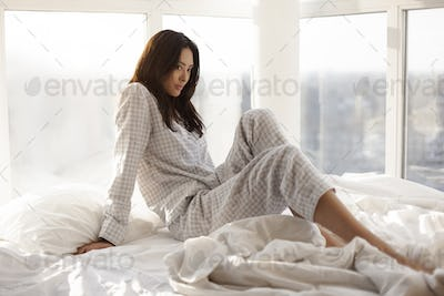 Asian Woman sitting in the Bed Indoors