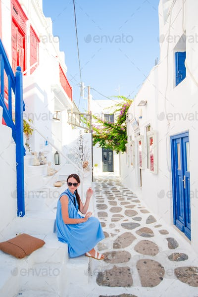 Caucasian tourist walking along the deserted streets of greek village