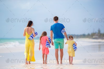 Back view of a young family on tropical beach
