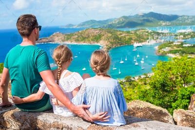 Adorable little kids and young father enjoying the view of picturesque English Harbour at Antigua in