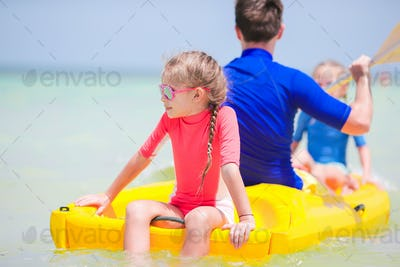 Little girls and young dad kayaking during summer vacation