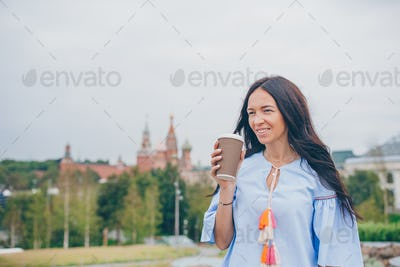 Happy young urban woman drinking coffee in european city