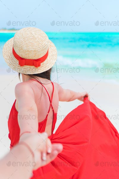 Young woman in hat during tropical beach vacation. Back view of happy girl enjoying her holidays