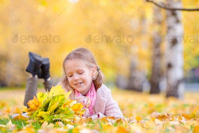 Portrait of adorable little girl with yellow leaves bouquet in fall. Beautiful smiling kid lying on
