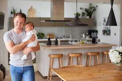 Portrait Of 3 Month Old Baby Daughter Being Held By Loving Father In Kitchen At Home