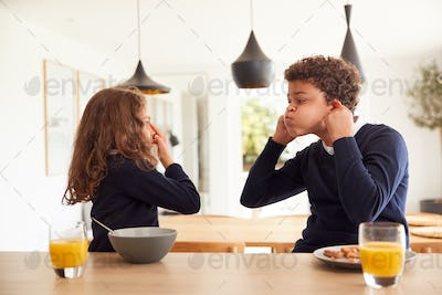 Children At Kitchen Counter Eating Breakfast And Pulling Faces Before Going To School