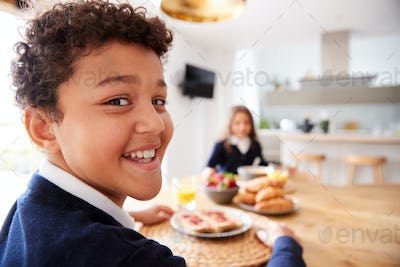 Portrait Of Children Wearing Uniform In Kitchen Eating Breakfast Before Going To School