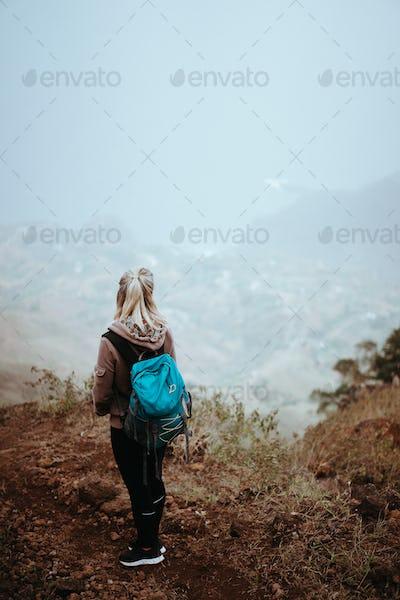 Female hiker looking down over a vertiginous misty ridge on the route to Coculi. Santo Antao Cape