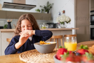 Girl Wearing Uniform In Kitchen Eating Breakfast Cereal Before Going To School