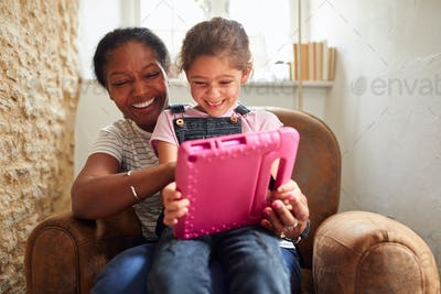 Grandmother Sitting In Chair With Granddaughter Watching Movie On Digital Tablet Together