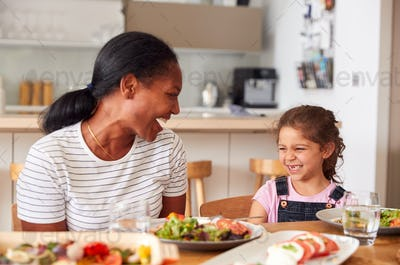 Grandmother And Granddaughter Laughing As They Eat Meal At Table