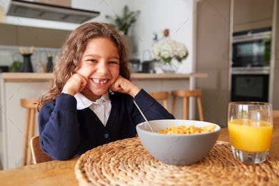 Portrait Of Girl Wearing Uniform In Kitchen Eating Breakfast Cereal Before Going To School