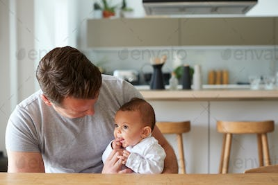 Loving Father Holding 3 Month Old Baby Daughter In Kitchen At Home