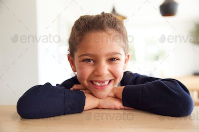 Portrait Of  Girl Wearing School Uniform Leaning On Kitchen Counter