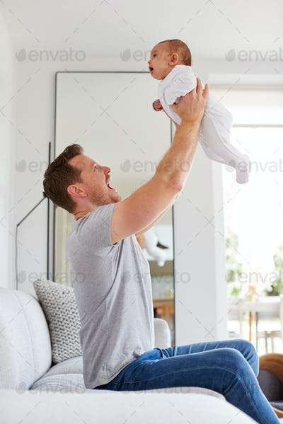Loving Father Lifting 3 Month Old Baby Daughter In The Air In Lounge At Home