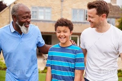 Father With Son And Grandfather From Multi-Generation Mixed Race Family Walking In Garden At Home