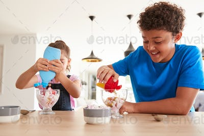 Children In Kitchen At Home Adding Sprinkles And Sauce To Ice Cream Dessert