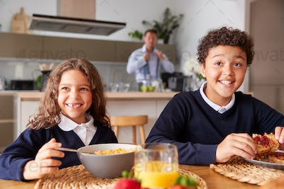 Portrait Of Children Wearing School Uniform Eating Breakfast As Father Gets Ready For Work