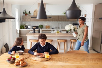 Mother In Kitchen Helping Children With Breakfast Before Going To School