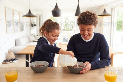 Children At Kitchen Counter Eating Sugary Breakfast Before Going To School
