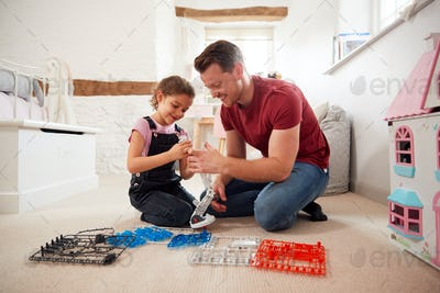 Father And Daughter In Bedroom Building Robot Kit Together