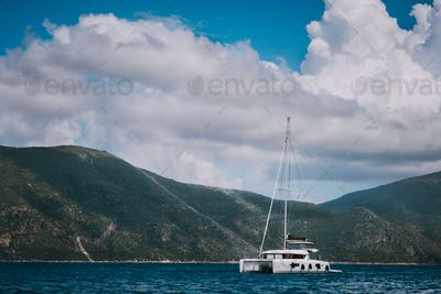 Catamaran ship in open sea near Fiskardo. Big clouds moving over the mountain shape of Ithaki island
