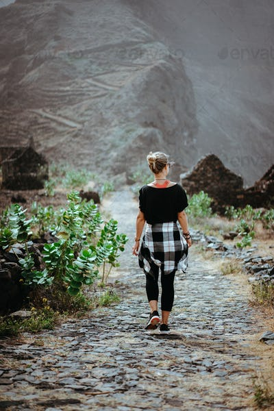 Woman hiker on the picturesque coastal cobbled route. The road joins the towns of Cruzinha