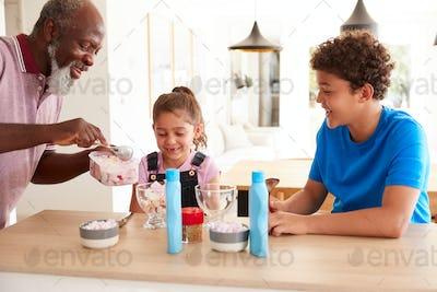 Grandfather Serving Ice Cream To Grandchildren In Kitchen