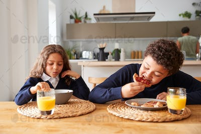 Children Wearing Uniform In Kitchen Eating Breakfast Before Going To School