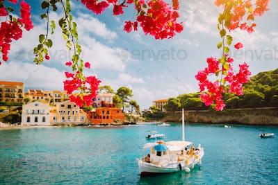 Kefalonia Greece Assos village, fishing boat in tranquil bay and magenta fuchsia blossom