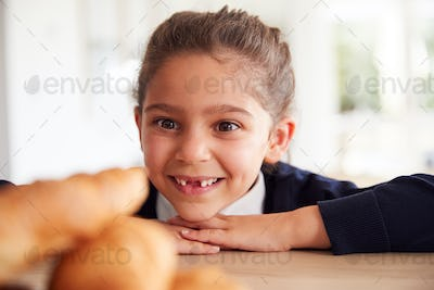 Mischievous Girl Wearing School Uniform Taking Croissant From Kitchen Counter